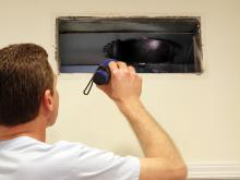 Man looking inside of a vent with a flashlight in Wall Township, NJ to clean it